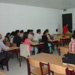 Studenci siedzący w sali podczas wykładu - widok z tyłu