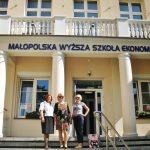 Trzy kobiety na schodach przed budynkiem uczelni