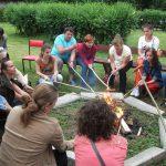 Uczestnicy siedzą w kole, pieką kiełbaski przy ognisku