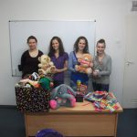 Cztery studentki pozują z misiami pluszowymi na biurku zebrane zabawki i artykuły biurowe