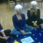 Dwie studentki siedzące po turecku na dywanie, na głowach kaski z folii aluminiowej