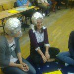 Dwie studentki siedzące na dywanie, na głowach kaski z folii aluminiowej