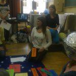 Studentka klęczy na dywanie, prezentuje planety w układzie słonecznym