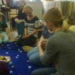 Studentki pedagogiki klęczące na dywanie podczas prezentacji układu słonecznego