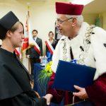 Rektor wręcza dyplom ukończenia studiów wyróżnionej studentce