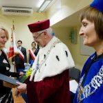 Rektor wręcza dyplom ukończenia studiów wyróżnionej absolwentce studiów podyplomowych