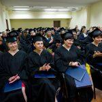 Wyróżnieni absolwenci w togach i biretach