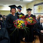 Dwie absolwentki i absolwent z bukietami kwiatów