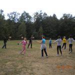 Grupa studentów wykonuje ćwiczenia na łące, w tle widoczny las