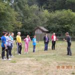 Grupa studentów stoi na łące słuchając instruktora, w tle las