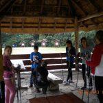 Studenci podczas przygotowania i sprawdzania sprzętu - kijków stoją pod drewnianą wiatą