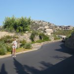 Studentka stoi przy drodze wiodącej do zabudowań