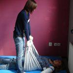 Doula prowadzi masaż ciężarnej chustą
