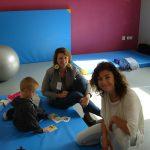 Dwie kobiety i dziecko - wszyscy siedzą na rozłożonym na podłodze materacu gimnastycznym