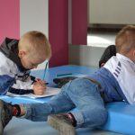 Troje dzieci leży na materacu na brzuchach i rysuje