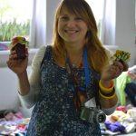Uśmiechnięta młoda kobieta w obu rękach trzyma słoiki z przetworamita