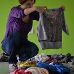 Kobieta kuca nad rozłożonymi na podłodze ubraniami w rękach trzyma rozłożony sweter