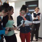 Grupa trzech młodych kobiet stoi z arkuszami ankiety i ołówkami w rękach