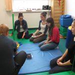 Studentki klęczą na materacu w sali do fizjoterapii