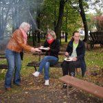 Trzy studentki na ławkach w otoczeniu drzew jedzą kiełbasę z ogniska