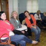 Trzy studentki soedzą na krzesłach w sali wykładowej w oczekiwaniu na rozpoczęcie warsztatów