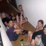 Grupa młodych ludzi siedzi na podłodze balkonu hotelowego