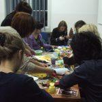 Uczestnicy siedzą przy stole, wykonują kartki świąteczne, na stole materiały