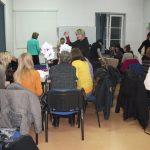 Uczestnicy siedzą przy stolikach, prowadząca objaśnia zadania