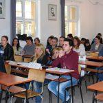 Studenci siedzą przy stolikach w sali wykładowej