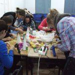 Studenci zgromadzeni przy stole wykonują ozdoby świąteczne, stół zastawiony materiałami