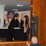 Na scenie auli kanclerz mgr Zofia Kozioł gratuluje organizatorce spotkania mgr Karolinie Chrabąszcz, obok nich stoi jeden z prelegentów, w tle za stołem prezydialnym stoi przedstawiciel firmy Open Finance