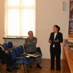 Kanclerz Zofia Kozioł zabiera głos stojąc, obok siedzą uczestnicy seminarium mgr Witold Zych i prof. Wasilij Rudnicki