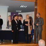 Na scenie auli od lewej stoją kanclerz mgr Zofia Kozioł, organizatorka seminarium mgr Karolina Chrabąszcz, jeden z prelegentów, w tle za stołem prezydialnym stoi jeden z przedstawicieli firmy Open Finance