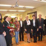 Zdjęcie grupowe. Prof. Elżbieta Skrzypek trzymająca bukiet róż w otoczeniu przedstawicieli władz i nauczycieli akademickich MWSE