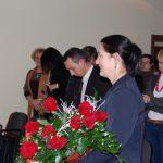 Kanclerz Zofia Kozioł z bukietem róż, w tle pracownicy akademiccy MWSE