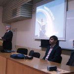 Pracownicy MWSE w uczelni partnerskiej w Bułgarii, za stołem siedzą od prawej prof. Leszek Kozioł, dr Wojciech Kozioł, stoi mgr Witold Zych, za ich plecami na ścianie ekran, na którym slajd z prezentacji oferty edukacyjnej MWSE