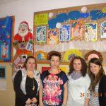 Cztery studentki stoją w szkolnym korytarzu przy ścianie, na której wiszą prace plastyczne dzieci
