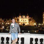 Noc, student stoi na tarasie opierając się o barierkę, w tle oświetlone budynki kasyna