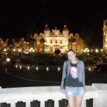 Noc, studentka stoi na tarasie opierając się o barierkę, w tle oświetlone budynki kasyna