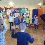 Dzieci, ustawione w okręgu naśladują ruchy prowadzącego