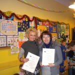 Wychowawczyni mgr Wiesława Krysa oraz mgr Marta Falińska stoją w klasie, prezentując dyplomy