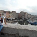Student stoi przy murku, w tle widok na port