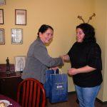 Kanclerz wręcza torebkę firmową z upominkami prof. Androniki Kavoura