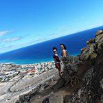 Dwie studentki stoją na zboczu wzniesienia, w tle plaża i ocean