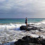 Studentka stoi na kamieniach na plaży, wokół ocean