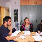 Dwie studentki i student siedzą przy stole w trakcie zajęć