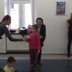 Dziewczynka trzymana za ramiona przez panią kanclerz otrzymuje słodycze od studentki