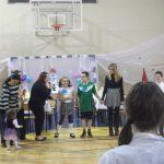 Dzieci i opiekunowanie stoją w kole na sali gimnastycznej, studentka z Koła tłumaczy zasady następnej zabawy