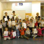 Grupowe zdjęcie dzieci, wychowawców z kanclerz Uczelni - dzieci prezentują otrzymane dyplomy