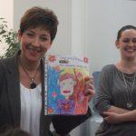 Wicelanclerz Renata Mielak prezentuje narysowany przez dzieci portret, obok pracownik działu mgr Weronika Budzik